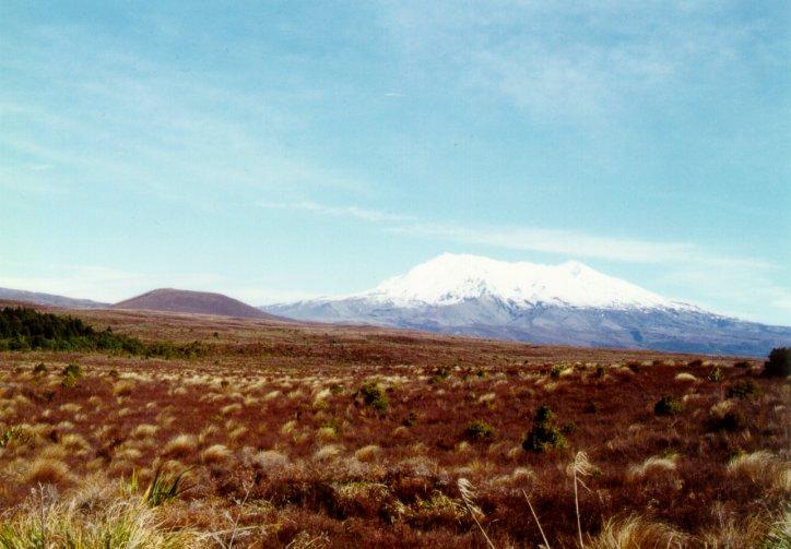 Vulcão Ruapehu. Observar o cume da montanha coberto por neve e um pequeno